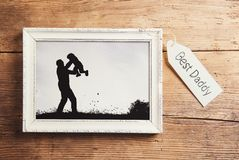 Fathers day composition. Picture frame with a black and white photo. Studio shot on wooden background royalty free stock photography