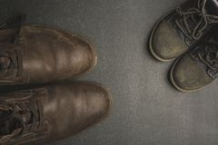 Daddy's boots and baby's shoes, fathers day concept. Fathers day concept. Big and small shoes Royalty Free Stock Photo