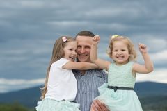 Fathers day concept. Father hold daughters on cloudy grey sky. Man and girls happy smile on summer day in mountain royalty free stock image