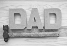 Fathers day concept. Letters spelling dad and a hammer on wooden background stock image