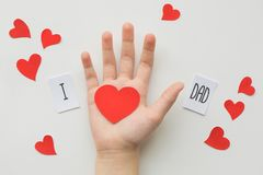 Fathers day concept. Message with paper heart in childrens hand on white background. Top view. Birthday royalty free stock photography