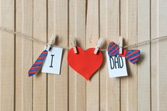 Fathers day concept. Message with paper hearts, tie and bow-tie hanging with pins over light wooden board. Happy Birthday royalty free stock photo