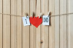 Fathers day concept. Message with paper heart hanging with pins over light wooden board. Happy Birthday. Fathers day concept. Message with red paper heart royalty free stock image