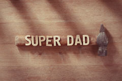 Fathers day concept. Old hammer on a wooden table with Super Dad text. Happy holiday. Royalty Free Stock Photo