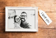 Fathers day concept. Picture frame. Wooden background. Fathers day concept. Photo of father and daughter in white picture frame. Studio shot on wooden Royalty Free Stock Photos