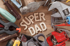 Fathers day concept. Set of old tools on a wooden carpenter desk with Super Dad text. Happy holiday. Royalty Free Stock Image