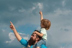 Fathers day. Cute boy with dad playing outdoor. Happy child pointing on summer sky background. royalty free stock image