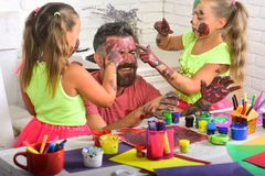 Fathers day and family concept. Daughters and dad smiling with painted hands. Creativity and imagination. Girls drawing on men face skin with colorful paints stock photo