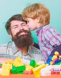 Fathers day. Father and son have fun with bricks. Bearded hipster and boy play together. Dad and child build of plastic. Blocks. Child care concept. Happy stock photography
