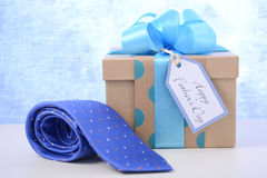 Fathers Day gift and ite. Happy Fathers Day gift and necktie on white wood table and pale blue background stock photo