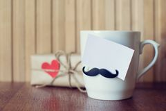 Greeting card on Cup with funny mustache over wooden board. Fathers day. Happy birthday. Valentines day. Mockup stock photos