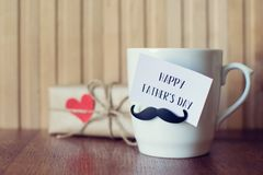 Fathers day. Greeting Message, Cup with funny mustache over wooden board. Fathers day. Greeting Message card on the Cup with funny mustache over wooden board royalty free stock photo
