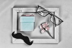 Fathers day. Homemade gift box, the symbols of Father`s Day-glasses, mustaches, roses. CONCEPT congratulation AND GIFTS. Composit. Ion in a frame.top view Stock Photography