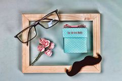 Fathers day. The inscription FOR THE BEST DAD on a self-made gift box, the symbols of Father`s Day are glasses, mustaches, roses. Royalty Free Stock Image