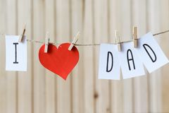 Fathers day message with paper heart hanging with pins over light wooden board. Happy Birthday stock photography