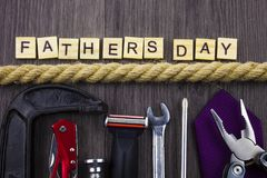 Fathers Day message on a wooden background with set of tools and ties, seperated by rope. Celebration. FATHERS DAY royalty free stock image