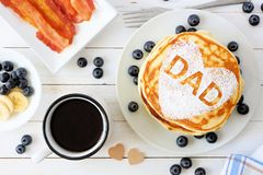 Fathers Day pancake breakfast with heart shape and DAD letters, above view table scene on white wood. Fathers Day pancakes with heart shape and DAD letters royalty free stock image