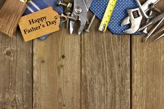 Fathers Day tag with tools and ties border on wood. Happy Fathers Day gift tag with top border of tools and ties on a rustic wood background Royalty Free Stock Photos