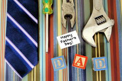 Fathers Day theme. Collection of tools with tie and Fathers Day tag over a masculine patterned background royalty free stock images