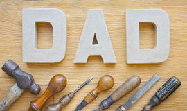 Fathers Day Tools. Letters spelling dad and a set of old tools on a wooden background stock photos
