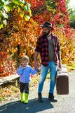 Fathers love for son. Retro style - Father with a suitcase and his son. Dad with young son in autumn park. Travels. Concept stock images