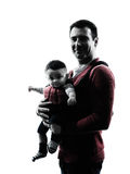 Fathers parents with baby carrier silhouette Stock Images
