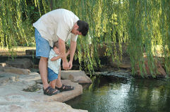 Fathers and sons. Father takes his son to explore nature and the creek. Looking for fish. Throwing and pointing royalty free stock photo