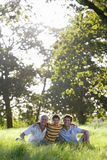 Fathers and sons sitting in field Stock Photo