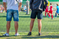 Fathers watching their sons playing soccer game Stock Image