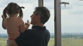 Fathr e a filha estão observando a vista através da janela filme