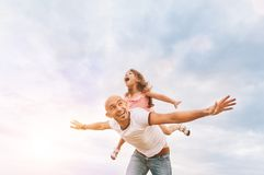 Fathrer and cute daughter playing like airplane. Fathrer and cute daughter sitting on his back and playing like airplane. Bright summer sunny day, happy faces royalty free stock image
