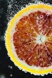 Fatia alaranjada do citrino que cai na água Imagens de Stock
