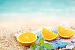 A fatia alaranjada fresca dos segmentos com a hortelã no mar da tela e da areia encalha o dia de verão Imagens de Stock