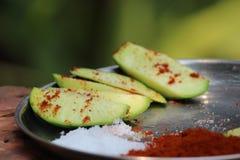 A fatia crua da manga com sal e o pimentão vermelho temperam a foto foto de stock
