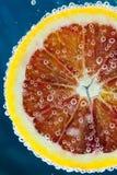 Fatia da laranja pigmentada que cai na água Imagens de Stock