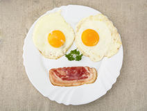 Fatia de bacon com os dois ovos na placa como a cara Fotografia de Stock