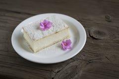 fatia de bolo de queijo decorada com violetas Fotografia de Stock