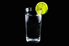 Fatia de cal em refrescar o vidro frio da água no fundo preto Fotografia de Stock Royalty Free