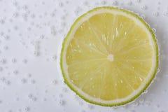 Fatia de cal fresco na água com bolhas Foto de Stock