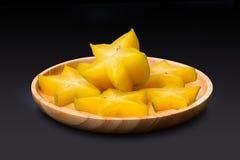 Fatia de fruto de estrela amarelo na bandeja redonda de madeira isolada no fundo preto fotografia de stock