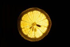 Fatia de limão maduro isolada em um fundo escuro Foto de Stock