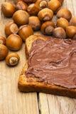 Fatia de pão com chocolate com as avelã na madeira Imagens de Stock Royalty Free