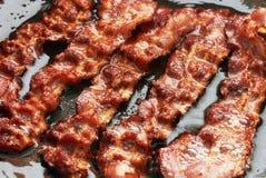 Fatia do bacon que está sendo cozinhada na frigideira Fotos de Stock Royalty Free