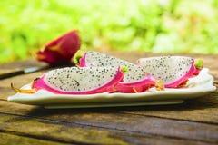 Fatia do fruto do dragão no prato branco no fundo de madeira velho da tabela e da natureza Fotos de Stock