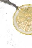 Fatia do limão que cai na água fotografia de stock royalty free