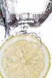 Fatia do limão que cai na água imagem de stock royalty free