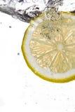 Fatia do limão que cai na água fotos de stock royalty free
