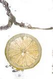 Fatia do limão que cai na água Imagem de Stock