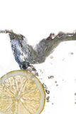 Fatia do limão que cai na água foto de stock