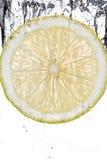 Fatia do limão que cai na água imagens de stock